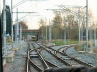 Driver's view of the now connected and operational junction for the new Manchester Airport tram line at St Werburgh's Rd. The tram is about to diverge from the old railway formation onto brand new tracks and a Metrolink service from East Didsbury is being held while the Airport service crosses the Up line. [See image 44201] for the same location in 2013.<br><br>[Mark Bartlett&nbsp;02/12/2014]