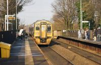 A Manchester Victoria to Leeds semi fast service passes Mills Hill in east Manchester on 29 November 2014 as passengers wait on both platforms for the next stopping services.<br><br>[John McIntyre&nbsp;29/11/2014]