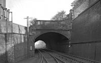 Old undated photograph looking north west through Ladhope Tunnel (which in reality is a wide bridge to accommodate a very skew crossing under the A7 road). Note the connection to a siding which once existed on Ladhope Vale in Galashiels. Early 20th century OS maps show It serving a loading dock, although its precise purpose is not obvious. Also of interest is the shanty building above the tunnel mouth - no doubt it housed workshops of some sort. The bridge itself was to see many changes in the years ahead [see image 22401].<br><br>[Bill Jamieson Collection&nbsp;//]
