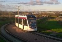 The low winter sun illuminates both the buildings of Edinburgh Airport in the background and the tram negotiating the sharp curve as it approaches the Ingliston Park and Ride stop en route to the city.<br><br>[Malcolm Chattwood&nbsp;05/12/2014]