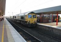 Freightliner 66506 heads north through Wigan North Western on 2 December 2014 with a rake of coal empties from Fiddlers Ferry. Over on Platform 5 a Northern Sprinter waits to return to Liverpool Lime St via St. Helens, a route that went over to EMU operation during 2015. <br><br>[Mark Bartlett&nbsp;02/12/2014]
