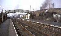 Platform view north through Kirkconnel station on 2 April 1965. On the right beyond the fence are the exchange sidings serving Fauldhead Colliery, the junction for which stands between the end of the up platform and the signal box. Fauldhead Colliery closed in 1968 [see image 33171].<br><br>[John Robin&nbsp;02/04/1965]