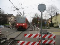 A service for Uetilberg [see image 49615] on the level crossing at Freisenberg in the Zurich suburbs in November 2014. Note the mish-mash of overhead wires - the road carries Zurich trolleybus route 32.<br><br>[Michael Gibb&nbsp;30/11/2014]