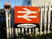 The large and rather unusual station sign by the level crossing at Dolau Station, on the Heart of Wales line, mounted on the well worn fence at the rear of the disused northbound platform.  <br><br>[David Pesterfield&nbsp;10/04/2012]