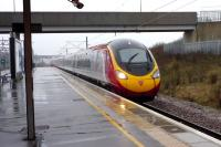 The 1300 London Euston - Manchester Piccadilly Virgin Pendolino service runs north through a wet Milton Keynes Central at speed on 3 January 2015.<br><br>[John Steven&nbsp;03/01/2015]