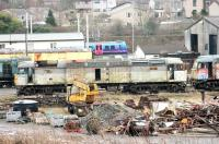 A tired and well worn 47368 stands in the scrap and recovery area at Carnforth Depot on 5 January 2015. The ex-Fragonset Brush 4 was purchased by West Coast in late 2006 but hasn't run since and is slowly losing its components to other West Coast operational locos. [See image 40169] A Barrow bound TPE 185 runs past the site in the background.<br><br>[Mark Bartlett&nbsp;05/01/2015]
