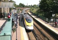 The West London Line platforms at West Brompton looking south from Old Brompton Road in July 2005. Passengers awaiting a Watford - Brighton train on platform 3 stand well back (apart from one eejit) as a 'eurostar' runs through empty on its way from North Pole to Waterloo. A District line train from Wimbledon has recently arrived at platform 2. [See image 37756]<br><br>[John Furnevel&nbsp;22/07/2005]