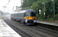 The pantograph of a Heathrow Express exerts a squeegee effect on the overhead wire as it speeds through Ealing Broadway in a rainstorm in July 2005 heading for the airport.<br><br>[John Furnevel&nbsp;20/07/2005]