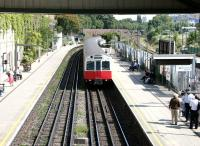 A Wimbledon - Barking District line train approaching West Brompton station on a warm and sunny afternoon in July 2005. West London Line platforms 3 & 4 stand to the right beyond the metal fence.  <br><br>[John Furnevel&nbsp;22/07/2005]