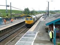 Freightliner 66617 brings a southbound cement train through Alnmouth station in May 2004. <br><br>[John Furnevel&nbsp;27/05/2004]