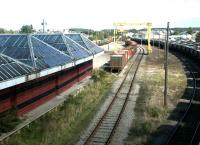 View northeast from the road bridge over Elgin East station and Yard in September 2004. The former locomotive shed, now in use as commercial premises, stands in the background beyond the stored wagons.<br><br>[John Furnevel&nbsp;12/09/2004]