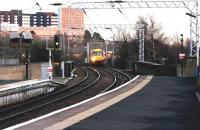 Platform view east from Partick station on a February afternoon in 2005 as a train for Milngavie approaches. Yorkhill Hospital stands in the left background.<br><br>[John Furnevel&nbsp;23/02/2005]