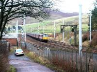 An up Virgin WCML express passing the site of Abington station on 7 December 2002, with Station Road curving away bottom left towards the village. The modern looking buildings and the sidings beyond are used primarily in connection with PW/maintenance activity. [See image 6252]<br><br>[John Furnevel&nbsp;07/12/2002]