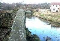 Looking north in 2003 over the remains of the southernmost of the two former railway bridges which spanned the Water of Leith between Powderhall and Bonnington stations [see image 3176].<br><br>[John Furnevel&nbsp;10/03/2003]