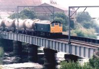 A northbound cement train crosses the doomed bridge over the River Caldew on the Carlisle goods lines shortly after passing through Rome Street Junction in July 1981. The Rome Street gasometer dominates the left background. Damage caused to this bridge by runaway Freightliner vehicles on 1 May 1984 led to final closure of the goods lines. <br><br>[John Furnevel&nbsp;11/07/1981]
