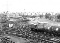 A Brush type 4 with a Freightliner is held at signals approaching Portobello East Junction off the sub in 1972. The train is standing below the bridge that carried the Lothian Lines on their way to Leith Docks. The Freightliner is waiting to cross the ECML and enter Portobello FLT, but the manoeuvre has been temporarily blocked due to the passing of an EE Type 3 with a train of tanks from Granton.<br><br>[John Furnevel&nbsp;30/10/1972]