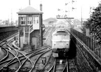 Scene at Dundee in September 1980 as a class 47 arrives with a Glasgow - Aberdeen train past Dundee West signal box.<br><br>[John Furnevel&nbsp;22/09/1980]
