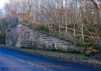 A January 2015 view showing the surviving southern abutment of the double track bridge that carried the railway over the A719 north of Maidens station and south of the goods yard. This section of the line closed completely in 1956.<br><br>[Colin Miller&nbsp;03/01/2015]