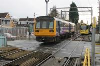 <I>On parallel lines.</I> Two services, both heading for Manchester Piccadilly, meet at Navigation Road on 13 January. Northern 142047, from Chester, runs over the level crossing, closely followed by Metrolink 3052. The Pacer will turn right at Deansgate Jnction to run via Northenden and Stockport while the tram service continues along the old MSJ&A route through Stretford. <br><br>[Mark Bartlett&nbsp;13/01/2015]