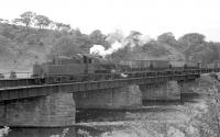 Scene at Ribton Bridge on the River Derwent, east of Camerton on the Workington - Penrith line in the 1950s. Ivatt 2MT 46489 has recently arrived with coal empties, which it is pushing back towards the sidings for Ribton Hall Colliery. The locomotive was based at Workington between 1954 and 1959 before moving to Upperby, from where it was withdrawn in November 1963. The line between Workington and Keswick closed in 1966. [Ref query 7169]<br><br>[Bruce McCartney Collection&nbsp;//]