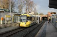 A Manchester bound tram (3070) calls at West Didsbury on 17th January. The original Withington & West Didsbury railway station, closed in 1961, lay just beyond the overbridge but the new tram station is much better located for the village centre.  <br><br>[Mark Bartlett&nbsp;17/01/2015]