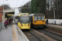 Two services for Manchester Piccadilly meet at Navigation Road. Pacer 142047 will travel via Stockport with three intermediate stops. Tram 3052 has 11 intermediate stops but a more direct route and both services will reach Piccadilly in just under thirty minutes.  <br><br>[Mark Bartlett&nbsp;13/01/2015]