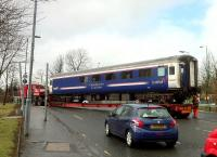 A Caledonian Sleeper Lounge Car emerging from the car park area at St. Rollox by road on 16 April 2013. The shiny new red springs suggest it has been receiving attention at RailCare.<br><br>[Colin McDonald&nbsp;16/04/2013]