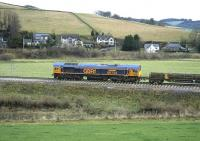 The first loco to pass in front of the photographer's house (the white one above the wagon bogie) after a gap of almost exactly 43 years - on 24 November 2014, 66752 waits just north of Stow station while two lengths of rail are winched off the rail laying train. While I cannot pinpoint the exact date that track was lifted here, that operation had reached milepost 27, about half a mile south of the station, on 22 November 1971, so there's a good chance that tracklifting was taking place here two days later.<br><br>[Bill Jamieson&nbsp;24/11/2014]