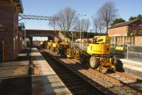 A lineup of road-rail aerial platforms for use on the Liverpool - Manchester electrification project parked on the reinstated but as yet unused platform 4 at Roby station on 3 February 2015. View west towards Liverpool Lime Street.<br><br>[John McIntyre&nbsp;03/02/2015]