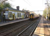 The platforms of Eccleston Park station on the Wigan to Huyton line on 3 February 2015, looking roughly south west as a Liverpool bound service passes through.<br><br>[John McIntyre&nbsp;03/02/2015]