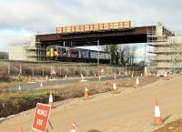 The deck of the new Heysham link road bridge was put in place over the WCML near Morecambe South Junction in January 2015. 150224 passes under the new structure on 9th February on a Morecambe to Leeds working that has just left the Morecambe branch. [See image 48728]  taken a few months earlier. <br><br>[Mark Bartlett&nbsp;09/02/2015]