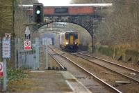 Looking north from the platform at Farnworth station on 5 February 2015 as a Northern service to Manchester Victoria approaches. Through the various bridges along this straight the up platform at Moses Gate station can just be made out.<br><br>[John McIntyre&nbsp;05/02/2015]