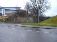 A substantial stone bridge abutment on the north side of Old Mill Lane, Barnsley, on the line connecting Court House Junction, beyond the building ahead, to Court House Station, behind the camera. A short isolated section of south side approach embankment stands on the right <br><br>[David Pesterfield&nbsp;16/02/2015]