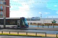 Starr Gate bound <I>Flexity</I> 002 leaves the Blackpool coastline briefly to go behind the Metropole Hotel before calling at the North Pier tram stop. The long overhang at the front of the Bombardier trams is very noticeable in this side view. North Pier also had its own tramway, but only from 1991 to 2004 when it was unfortunately closed and then scrapped.<br><br>[Mark Bartlett&nbsp;21/02/2015]