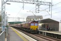 The gradient is evident along the line of wagons as 66066 attracts attention from waiting passengers at Cumbernauld station as it passes with a train of coal from Hunterston to Longannet on 5 March.  With more than 2000 tonnes on the drawbar it is unsurprising that the loco could be heard before it appeared.<br><br>[Malcolm Chattwood&nbsp;05/03/2015]
