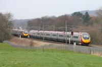 Two services running between Euston and Glasgow pass at the site of Brock water troughs just south of Garstang on 5 March. Both trains were formed by nine-car Pendolinos and timed at just under four and a half hours for the end to end journey.    <br><br>[Mark Bartlett&nbsp;05/03/2015]