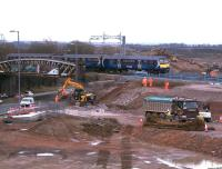 A Motherwell - Milngavie service approaches the site of the new Braehead viaduct on 6th March 2015. The temporary embankments and retaining wall of gabion baskets at the side of the railway line are nearing completion. Piling work for the replacement M8/Bredisholm Road overbridge is underway off picture to the right. Rail services should be unaffected by the works until the planned closure in July. <br><br>[Colin McDonald&nbsp;06/03/2015]