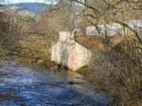 With less than half a mile to go before joining the Tweed, the Gala Water flows past the surviving northern abutment of the railway bridge that once carried the Selkirk branch across the river. Looking north west towards Galashiels station on 8 February 2015 from the pedestrian footbridge off Galafoot Lane. The recently laid tracks of the Borders Railway run between the mesh fences.<br><br>[John Furnevel&nbsp;08/02/2015]