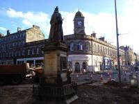 You can tell even from the back of her head that Queen Victoria is even less amused than usual that her eternal view of Leith Central station frontage is spoiled by the extensive road works currently going on at the foot of the Walk in March 2015.<br> <br><br>[David Panton&nbsp;12/03/2015]
