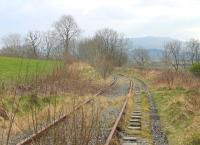 Looking south from the site of Festiniog station at Llan Ffestiniog towards Trawsfynydd in March 2015. The line closed in 1961 but reopened for traffic to the nuclear power station in 1964. The last flask train ran in 1998 when Trawsfynydd closed but the disused tracks remain. [Ref queries 2931 / 4434]  <br><br>[Mark Bartlett&nbsp;15/03/2015]
