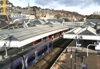 The 0833 Edinburgh - Dunblane runs into Stirling platform 2 on the morning of 1 April 2015. The red carpet beyond the train is part of an Abellio launch event to mark their takeover of the ScotRail franchise. At the top left of the picture Stirling Castle looks on impassively, having seen it all before.  <br><br>[John Furnevel&nbsp;01/04/2015]