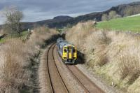 The 1426 Carlisle to Leeds service, formed of two Class 158s, approaches the footbridge at Langcliffe just north of Settle on Easter Saturday 2015. Pen-y-ghent is prominent in the background above the general landscape of the Ribble Valley.  <br><br>[Mark Bartlett&nbsp;04/04/2015]