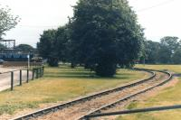 Looking over the curved track towards the former BOCM Unitrition grain processing plant at Selby in 2002, with the site's Unimog road rail vehicle over on the left at the head of a rake of eight loaded 2 axle high capacity wagons it has propelled from the overhead loading facility behind the camera. [See image 50763]<br><br>[David Pesterfield&nbsp;14/08/2002]