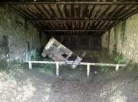 The inside of the catch pit at the bottom of Sheep Pasture Incline in March 2015, showing the remains of a wagon that demonstrates the value of the system.  The catch pit was installed in 1888 after two loaded wagons ran away almost from the top and were travelling at such speed they jumped the Cromford Canal and Midland Railway just beyond.  This particular wagon was safely arrested after its unrestrained journey down the bank in 1946. [see Image 50904]<br><br>[Malcolm Chattwood&nbsp;18/03/2015]