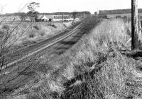Looking east along the Winchburgh Loop towards Dalmeny Junction in April 1972, with Winchburgh Junction behind the camera and the trackbed of Myre Siding to the right of the running lines. The few cottages in the middle distance constitute Myre itself. [Ref query 7596]<br><br>[Bill Jamieson&nbsp;/04/1972]