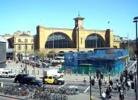 The market stalls have moved in and the blue mesh is back around the Kings Cross underground entrance building on 15 April 2015, the warmest day of the year so far. View from the eastern end of the St Pancras Station terrace.<br><br>[Andrew Wilson&nbsp;15/04/2015]