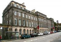 Opened in 1819 as the Waterloo Hotel, the building at 23 Waterloo Place was promoted as Edinburgh's 'first large scale hotel' with the strapline <I>'...an establishment where strangers can see the manners of the people and mix with the society of the place'</I>. The location was later to become, for many years, the Headquarters of the North British Railway Company. Now a category A listed building it has since reverted to its original use, this time under the name Apex Hotel, seen here on 14 April 2015. The Dugald Stewart Monument stands on Calton Hill in the right background.<br><br>[John Furnevel&nbsp;14/04/2015]