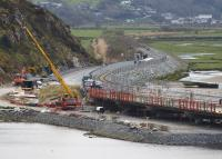 Progress at Pont Briwet on 17th April 2015: all traces of the original trestle bridge have gone and construction of the new concrete road bridge is well under way.<br> Llandecwyn station is complete and now has lighting and a Passenger Information System. [See image 49098]<br><br>[Colin McDonald&nbsp;17/04/2015]