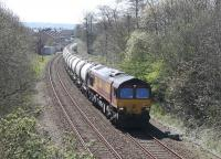 A train of cement empties from the Hanson siding at Avonmouth is on the last mile of a long journey on 18th April. DBS 66023 is approaching Clitheroe station and the nearby Ribble cement plant at Horrocksford where it will be loaded. [See image 42683]<br><br>[Mark Bartlett&nbsp;18/04/2015]