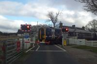 158703 heads southbound over the level crossing at Forsinard in April 2015.<br><br>[Rod Crawford&nbsp;23/04/2015]